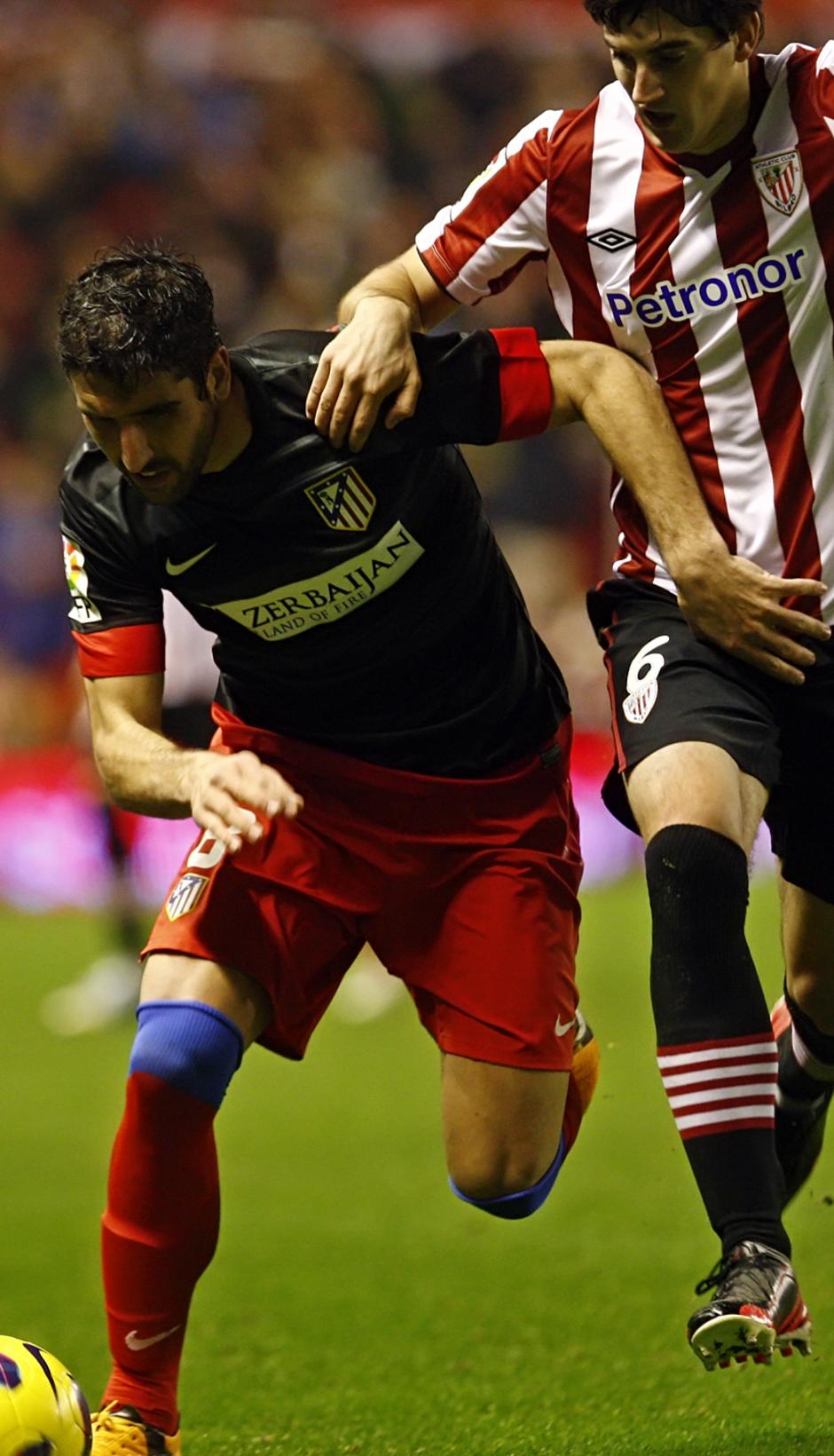 Raúl García peleando un balón con De marcos