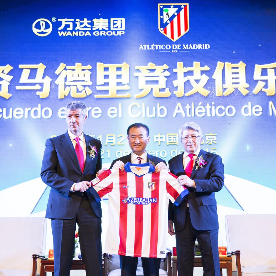 Miguel Angel Gil, Enrique Cerezo y Wang Jianlin posan con una camiseta del Atlético en Beijing
