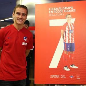 Griezmann posa junto al cartel que anima a los aficionados a llegar al Wanda Metropolitano por la línea 7