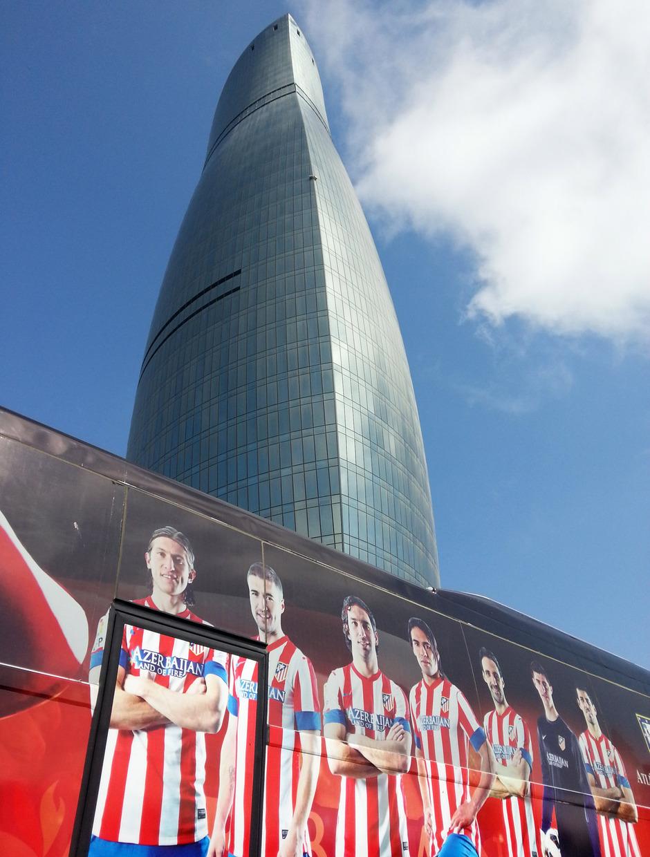 El bus personalizado del Atlético de Madrid delante de una de las torres del fuego