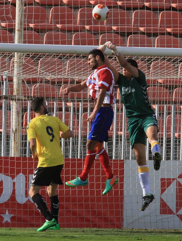 Kader, del Atlético B, intenta rematar un balón ante la oposición del portero de Las Palmas Atlético Alex