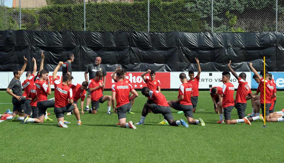 Los jugadores del Atlético Madrileño Cadete realizan estiramientos antes de iniciar el entrenamiento