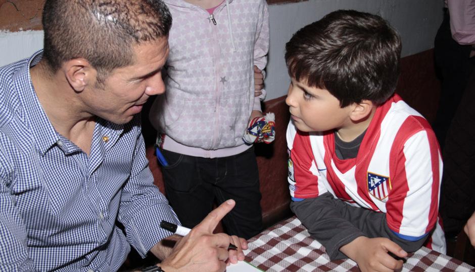 Simeone firma un autógrafo a un niño en la peña Cholo Simeone