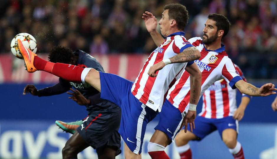 Temporada 14-15. Champions League. Atlético de Madrid-Olympiacos. Mandzukic intenta rematar a puerta ante un rival.