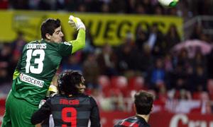 Temporada 12/13. Partido. Semifinales de la Copa del Rey. Courtois saltando a por un balón durante el partido en el Pizjuán