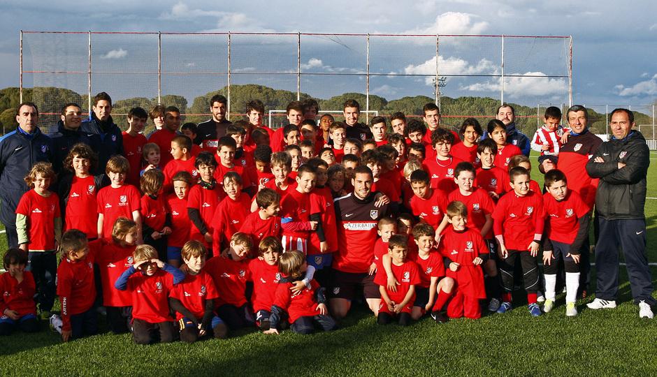 Los jugadores rojiblancos posan con los niños del Campus de la Fundación antes del entrenamiento del 27 de marzo