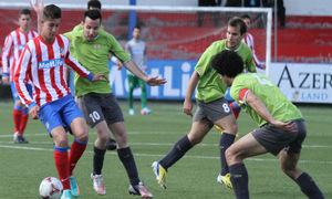 Ian, jugador del Atlético C, conduce el esférico ante varios jugadores del Adarve