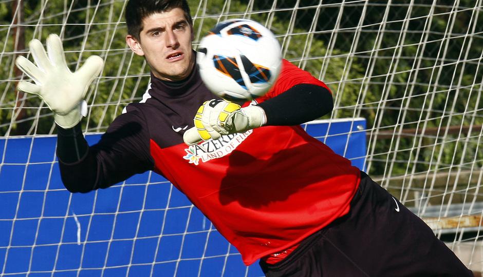 Thibaut Courtois no pierde de vista el balón al tiempo que se estira para atraparlo durante un entrenamiento