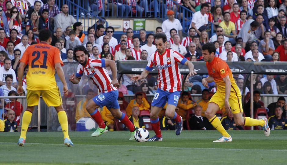 Temporada 12/13. Jornada 35. Atlético de Madrid - FC Barcelona. Juanfran conduce el balón ante la atenta mirada de Arda Turan y la presión de Fábregas