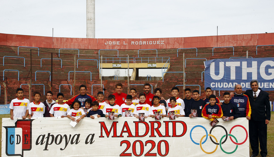 Temporada 12/13. Gira sudamericana. Visita al barrio Bajo Flores. Representación atlética Adrián pancarta  con niños