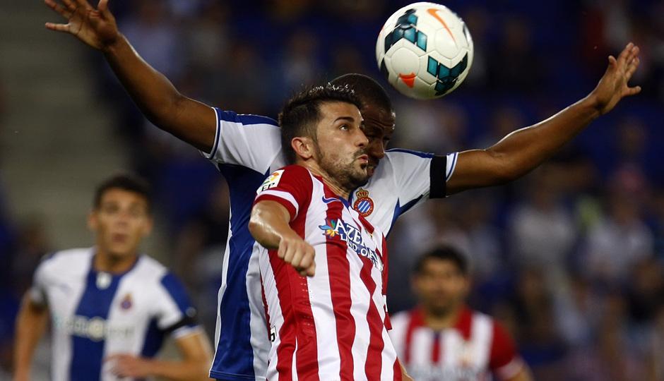 David Villa luchando por la posesión del balón con un jugador del Espanyol