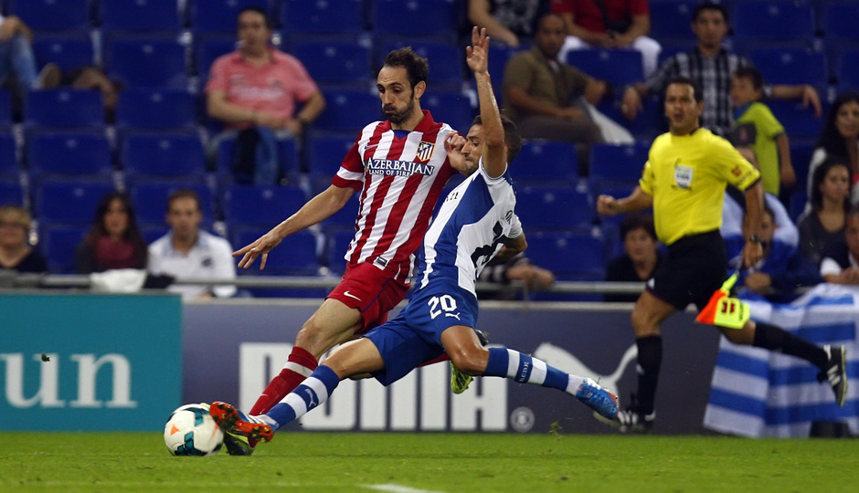 Juanfran conduce el balón ante la entrada de un jugador del Espanyol