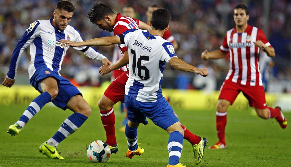 David Villa regateando a dos jugadores del Espanyol