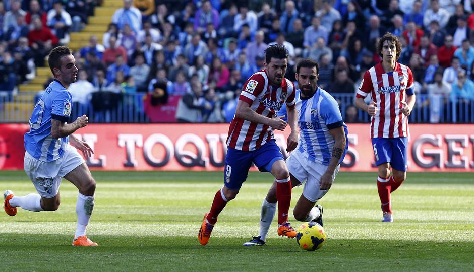 Temporada 13/14 Liga BBVA Málaga - Atlético de Madrid. David Villa se lleva el balón entre dos rivales.