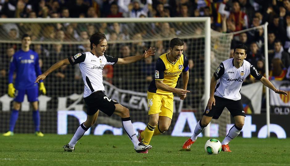 Temporada 13/14 Copa del Rey. Valencia - Atlético de Madrid. Gabi se marcha entre dos rivales.