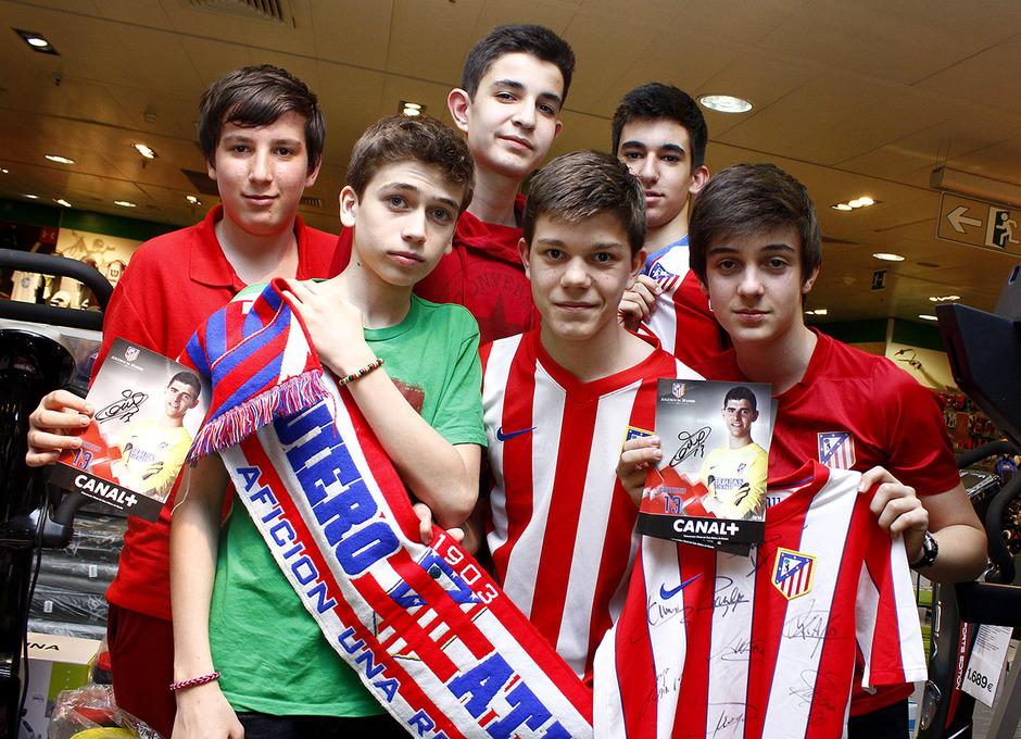 Un grupo de jóvenes posa con los colores del Atleti y la foto autografiada de uno de sus ídolos