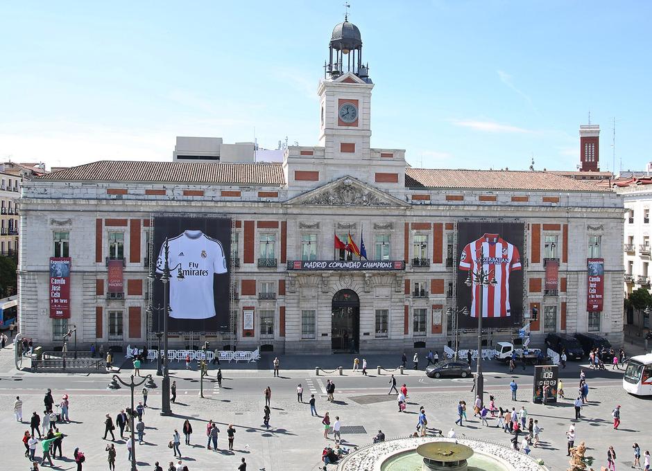 La fachada del Palacio de Correos, sede de la Comunidad de Madrid, ya vive la final de la Champions con las camisetas de Real Madrid y Atlético