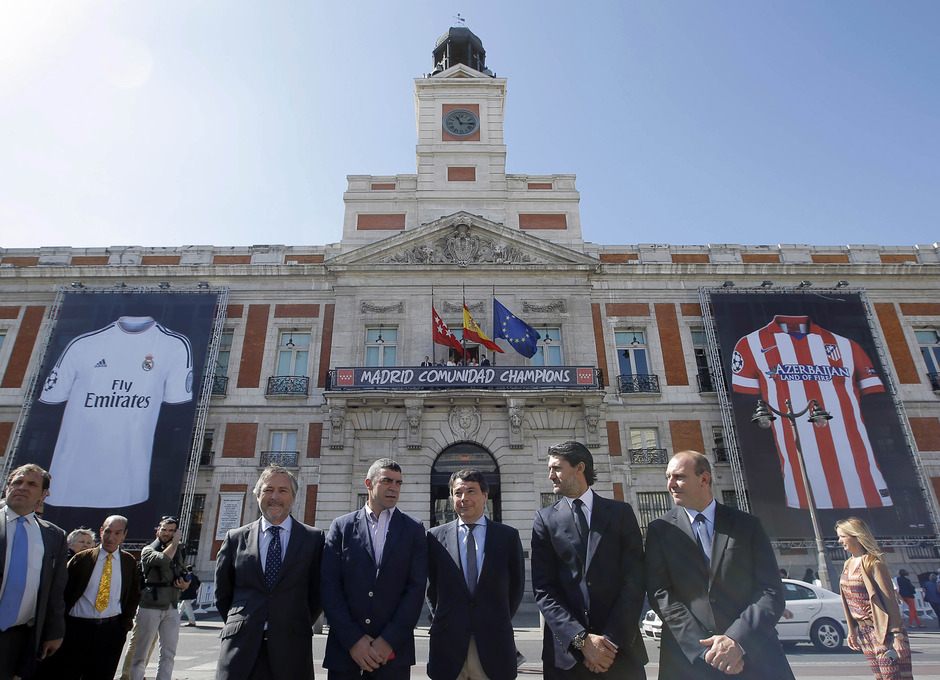 El presidente de la Comunidad, Ignacio González, posa en Sol con las camisetas del Atlético y del Madrid