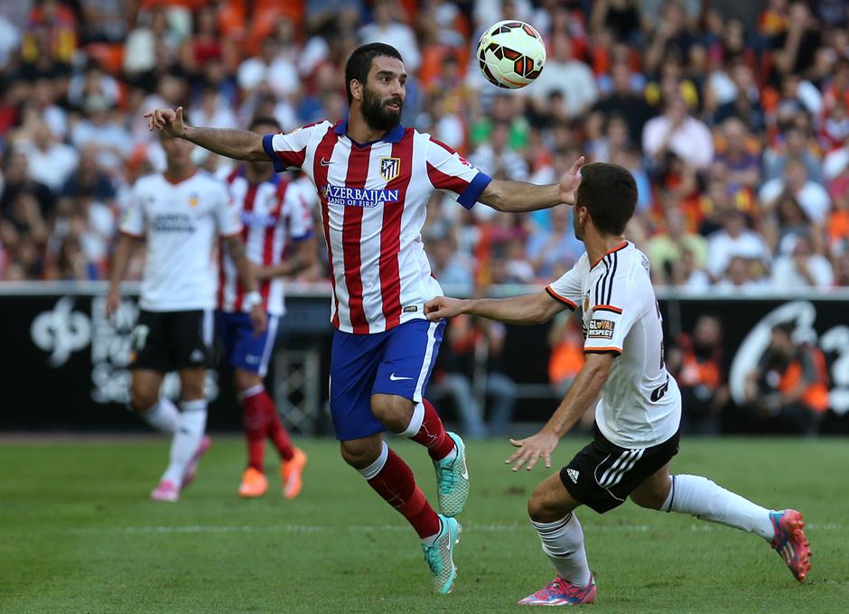 Temporada 14-15. Jornada 7. Valencia-Atlético de Madrid. Arda Turán salta de cabeza a por un balón.