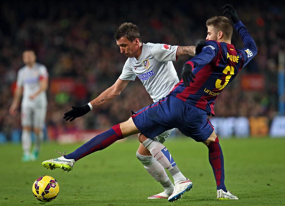 Temporada 14-15. Jornada 18. FC Barcelona-Atlético de Madrid. Mandzukic evita que Piqué le robe el balón.