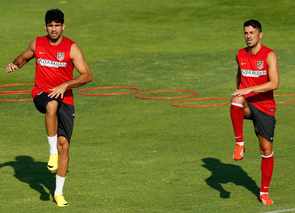 Diego Costa y Villa realizan estiramientos en el entrenamiento previo al desplazamiento a Sevilla