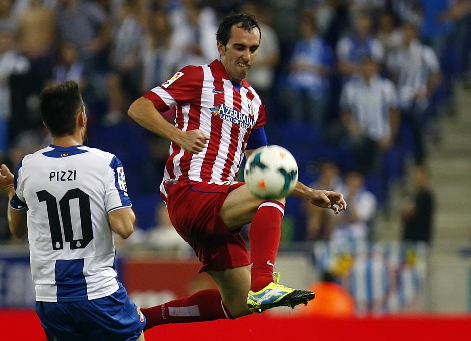Godín se lanza a por el balón ante la presencia de un jugador del Espanyol