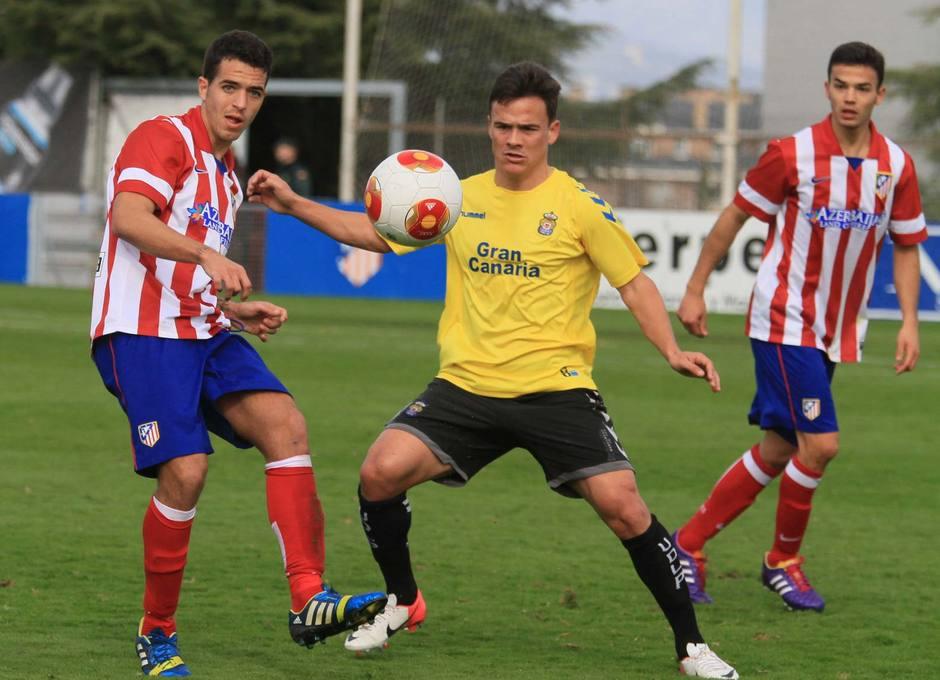 Vicente, jugador del Atlético B, da un pase en el partido contra Las Palmas Atlético ante la oposición del canario Roque