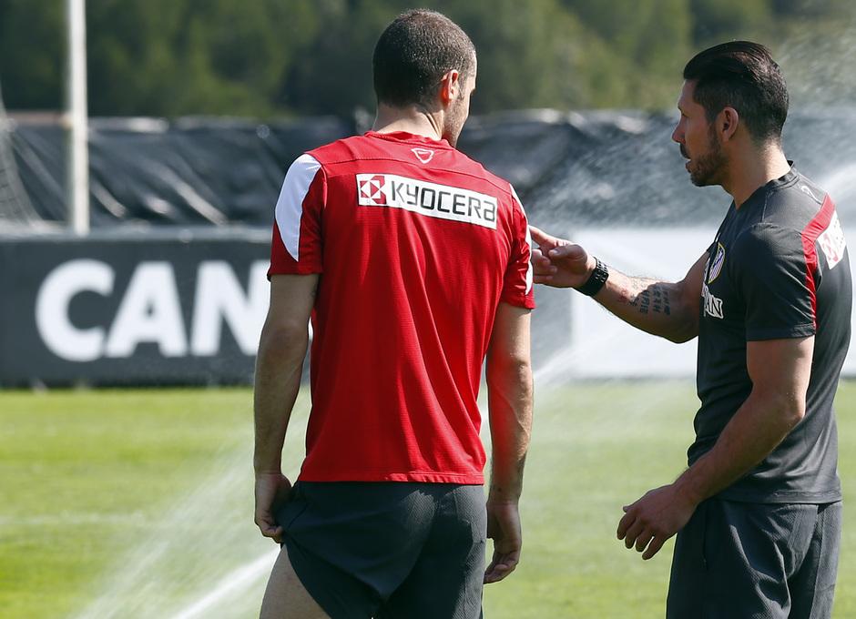 TEMPORADA 2013/14. Entrenamiento primer equipo en Majadahonda. Simeone y Mario Suárez dialogan tras finalizar la sesión de trabajo.