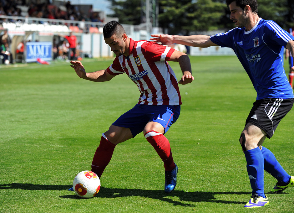 Rubén Mesa controla el balón ante la presión de un jugador del Laudio